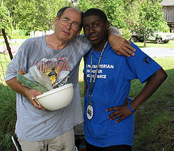 Photo of an older man with his arm around a young adult volunteer