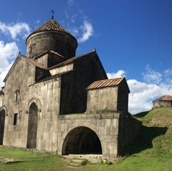 Stone Armenian church on green hillside under blue skies