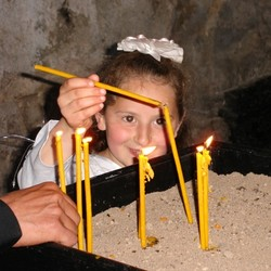 Young girl lights a prayer candle