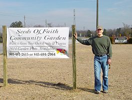 Fraser Memorial's former pastor Christopher Scott after standing up the new community garden sign Photo by Carol Clayton-Treadway