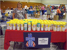 Elder Dena Burk handing out disinfecting wipes at a back-to-school fair Photo by Wendy Downing