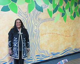 Alika Galloway, in front of a mural at NWS that includes a phrase from Revelation 22:2 Photo by Dennis Sanders