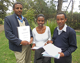 Mekane Yesus Seminary students Legesse, Almaz, and Tsegaye display their project proposals. Photo by Carolyn Weber