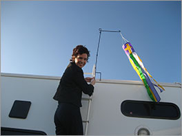 "Tamara John putting up the RV-park-ministry ""steeple,"" a flag with a cross Photo courtesy of Tamara John"