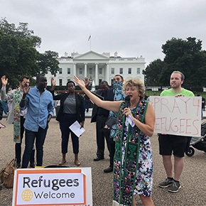 people praying with refugees welcome sign in front of white house