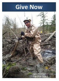 Give Button for Oso mudslide response; rescuer standing amidst mud