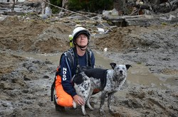Rescuer and dog in mud