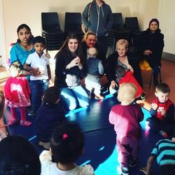teacher with children gathered around