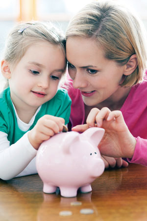 Mother, daughter and piggy bank