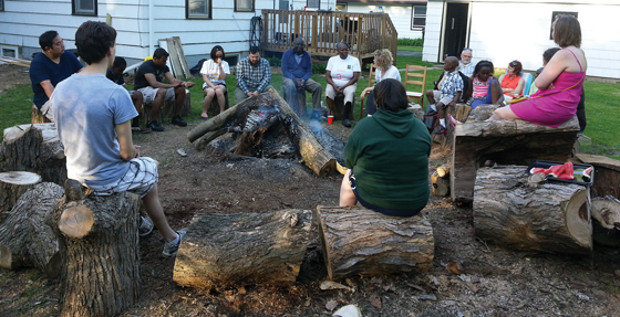 Underground Seminary students and instructors gather in a circle behind the Fink House, where students live in intentional community, integrating academic and daily life for the training of new leaders for the church.
