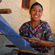 A woman weaving cloth with a loom