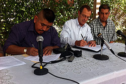 Three men sit at a table and sign a document