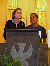 A woman and a man standing behind a podium