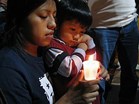 A woman and a child look at a lighted candle