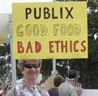 A man holding a sign that says Publix Good Food Bad Ethics