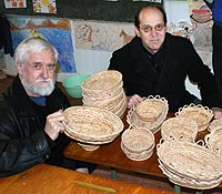 Two men sit at a table filled with handmade woven baskets
