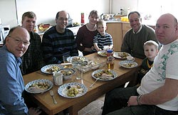 6 adults and 2 children sit at a table and eat a meal together