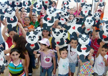 Children show off their art work at a JMP sponsored summer camp in Kessab, Syria.
