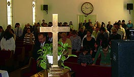 Photo of a congregation with the pews full of people